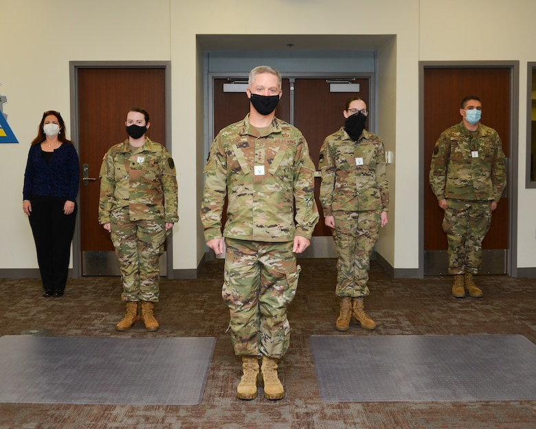 Airmen in uniform stand in a formation.