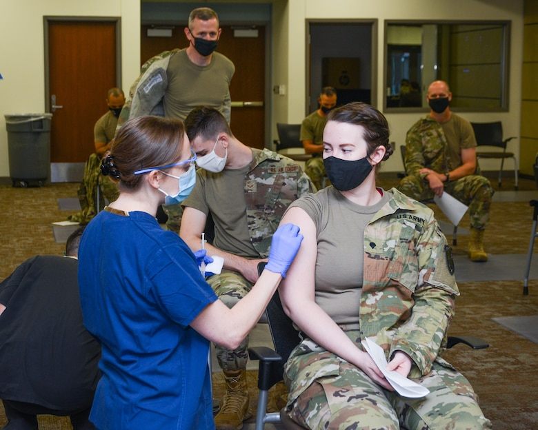 A female in an Army uniform receives a shot in her arm.