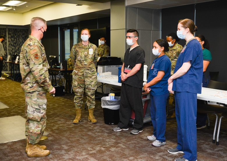 Lt. Gen. Timothy Haugh talks while standing in front of four medical center Airmen.
