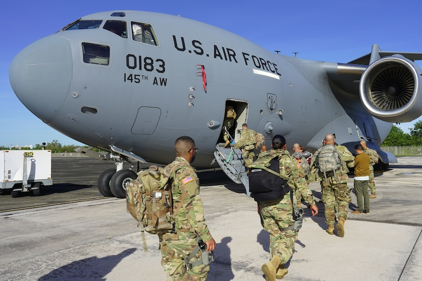 U.S. Army Soldiers with the 92nd Military Police Brigade, Puerto Rico Army National Guard, board a C-17 Globemaster III aircraft from the 145th Airlift Wing, to depart from Muñiz Air National Guard Base for Washington, D.C., in support of the 2021 presidential inauguration, Jan. 15, 2021.