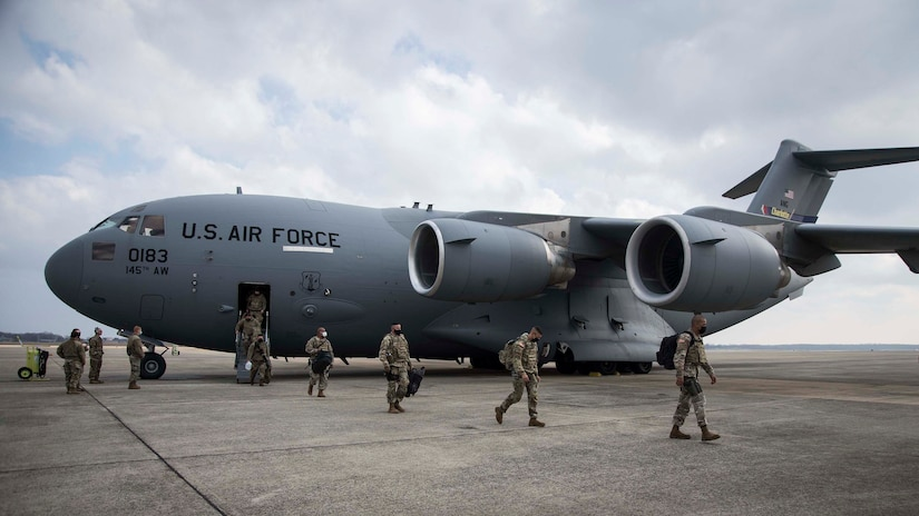 Members of the North Carolina National Guard deboard a C-17 Globemaster III, assigned to the 145th Airlift Wing, North Carolina Air National Guard, upon arrival to Joint Base Andrews, Md., Jan. 15, 2021. National Guard Soldiers and Airmen from numerous states have traveled to Washington, D.C., to support federal and district authorities leading up to the 59th presidential inauguration.