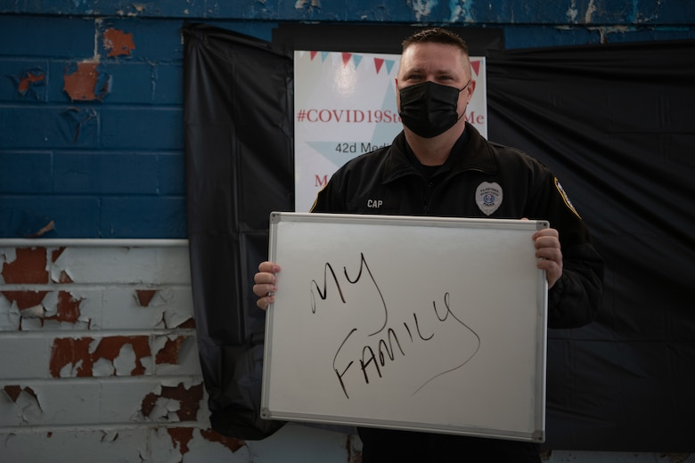 """Sgt. Richard Cap, a civilian defender and flight sergeant with the 42nd Security Forces Squadron, holds up a sign with his reason for getting the COVID-19 vaccine Jan. 16, 2020, at the off-site clinic in the Honor Guard hangar on Maxwell Air Force Base, Alabama. After receiving the vaccine, patients can take a photo at the """"I got the vaccine"""" selfie area."""