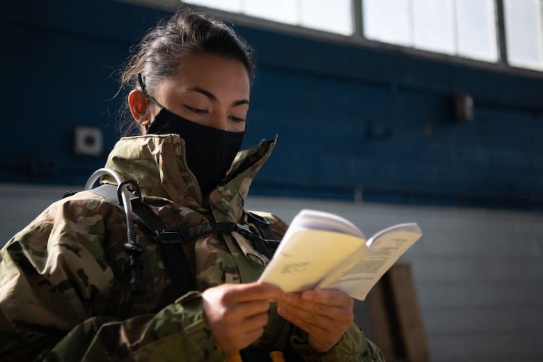 2nd Lt. Meggan Tamondong, an officer trainee at Officer Training School, reads an OTS manual while seated in the post-vaccination waiting area Jan. 16, 2020, at the off-site clinic in the Honor Guard hangar on Maxwell Air Force Base, Alabama. Patients were asked to remain in the hangar for an additional 30 minutes after receiving the vaccine so they could alert nursing staff if they had any concerns.