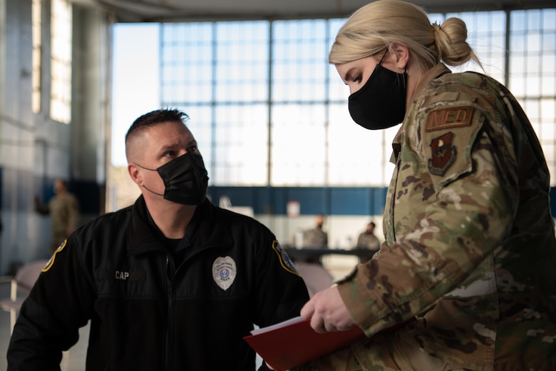 """Capt. Aphton Lane, 42nd Medical Group Operation Warp Speed team lead, explains the """"v-safe"""" program to Sgt. Richard Cap, a civilian defender and flight sergeant with the 42nd Security Forces Squadron, Jan. 16, 2020, at the off-site clinic in the Honor Guard hangar on Maxwell Air Force Base, Alabama. Recipients of the COVID-19 vaccine are encouraged to use the v-safe program to report any side effects and daily health to keep the vaccine process safe."""