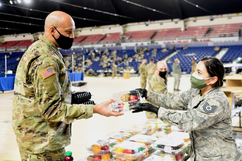Tech. Sgt. Jennifer Zamudio, a member of the District of Columbia Air National Guard, distributes a meal to a Soldier at the D.C. National Guard Armory, Washington, D.C., Jan. 10, 2021. National Guard officials are stressing that the Soldiers and Airmen from all 50 states, three territories and Washington are receiving adequate food and lodging as they continue to support federal and local authorities leading up to the 59th presidential inauguration.