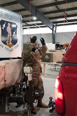 Tech. Sgt. Michael Lengle hooks up the Disaster Relief Mobile Kitchen Trailer to a vehicle in preparation to support service members in the D.C. area for the 59th Presidential Inauguration