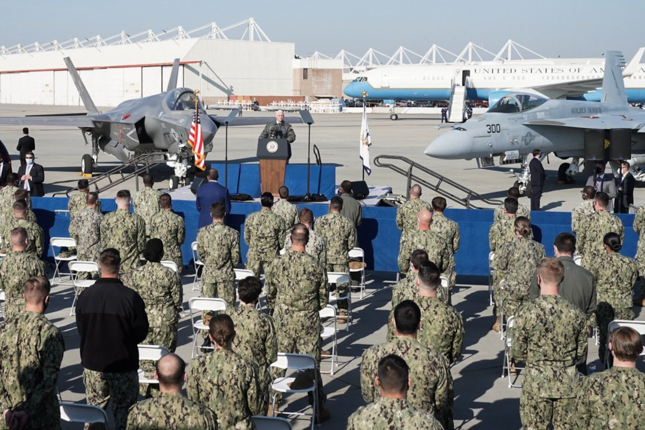 Service members stand beside their chairs on an airfield as a man standing on a stage in front of them speaks into a microphone.