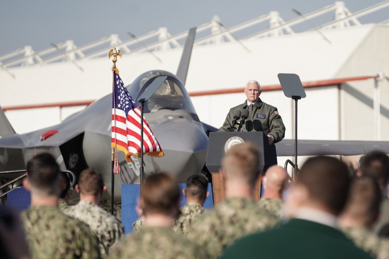 A U.S. flag waves in the breeze as a man stands behind a podium to speak; a jet is parked behind him.
