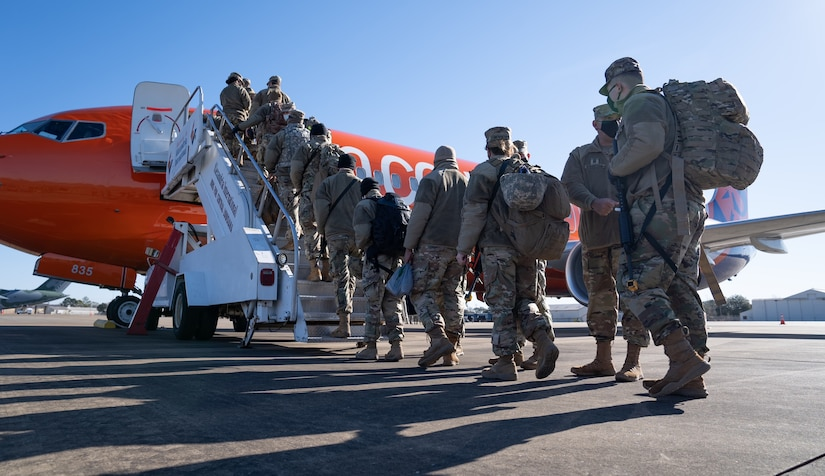 National Guardsmen are lined up to board a plane.
