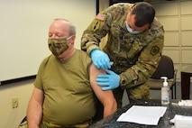 Brig. Gen. Michael J. Regan Jr., deputy adjutant general - Air, Pennsylvania National Guard, receives the COVID-19 vaccine from Master Sgt. Jose Martinez, a medical operations non commissioned officer with the Pennsylvania National Guard, on Jan. 13, 2021, at Fort Indiantown Gap, Pa.
