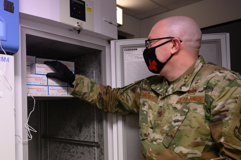 An Airman places COVID-19 vaccines into a freezer.