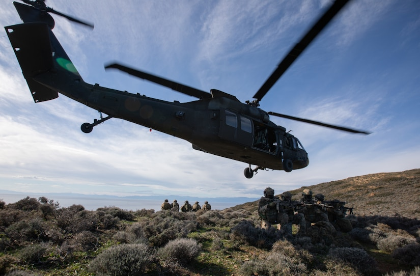A low flying helicopter flows over a group of soldiers on the ground.
