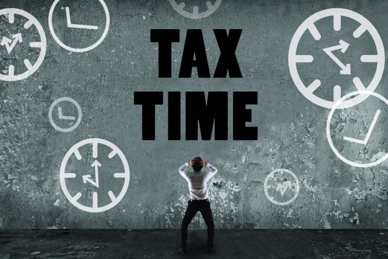 A graphic shows a man holding his head as he looks up at a large sign saying tax time.