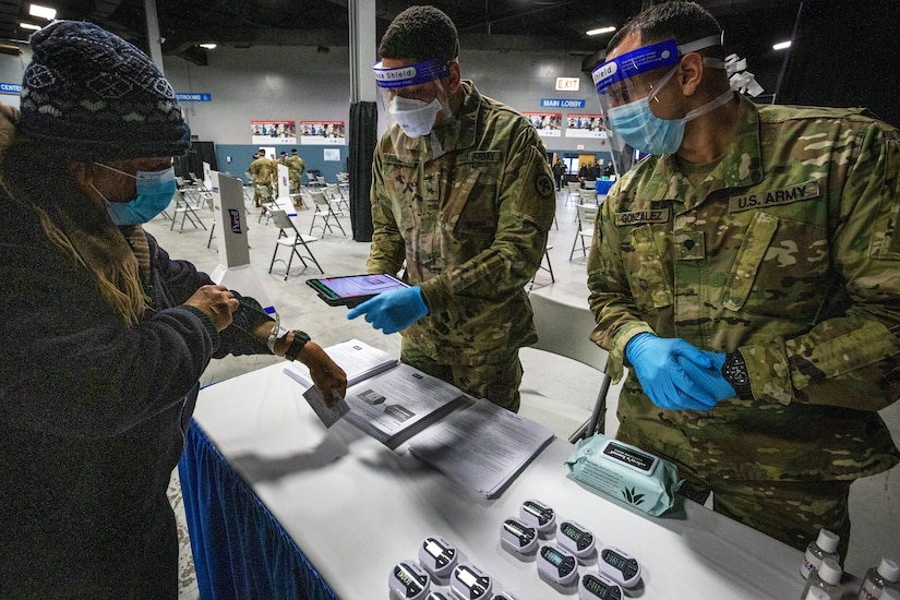 An Army soldier scans another soldier's COVID-19 vaccination card while another soldier watches.