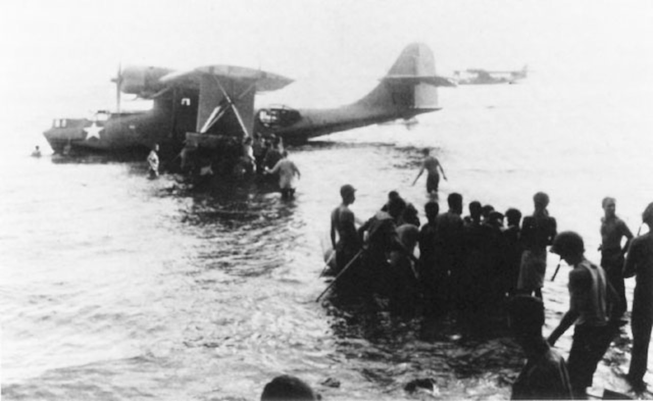 Troops wade to seaplane as it sits on the water.