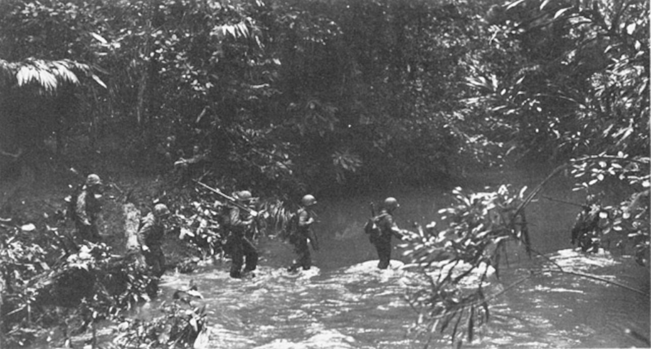 An historic photograph from 1943 shows Marines crossing a stream.