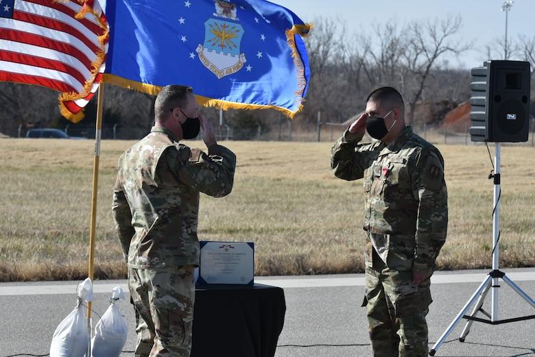Col. Filcek saluting Tech. Sgt. Lopez during ceremony