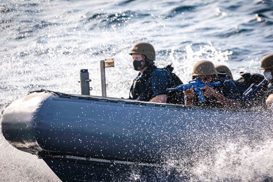 Sailors travel through water in an inflatable boat.