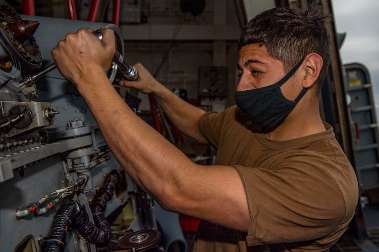 A sailor performs maintenance on a helicopter.