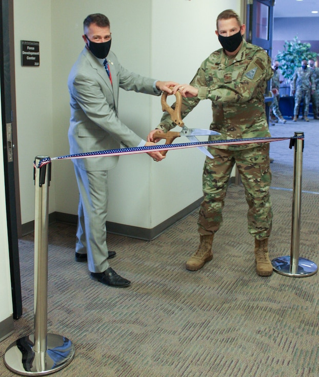 James Driscoll, 50th Force Support Squadron Development Flight chief, left, and Col. James Smith, Peterson-Schriever Garrison commander, prepare to cut a ribbon to commemorate the re-opening of the Force Development Center inside of Bldg. 210 at Schriever Air Force Base, Colorado, Jan. 12, 2021. Upgrades include sound-proof walls beneficial for testing and new spaces for staff and the center to hold the College Level Examination Program and the Dantes Subject Standardized Test.  (U.S. Space Force photo by Marcus Hill)