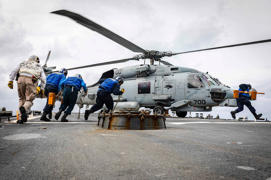 Sailors run toward a helicopter on the deck of a ship.