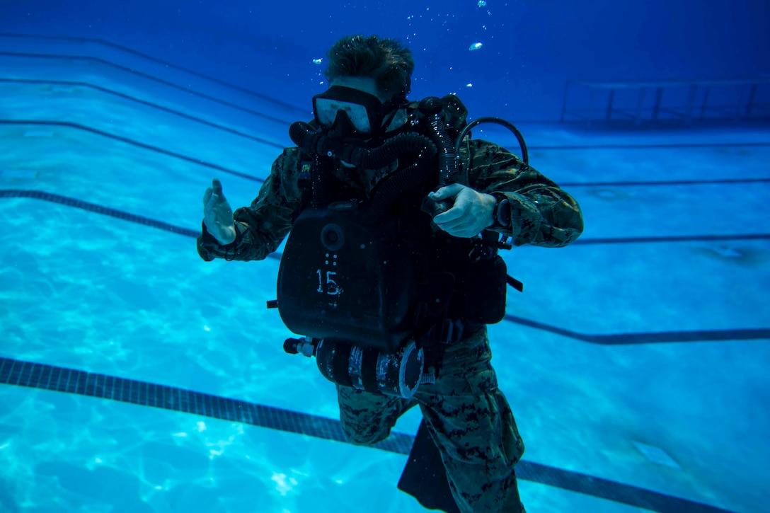 A Marine wearing dive gear dives underwater.