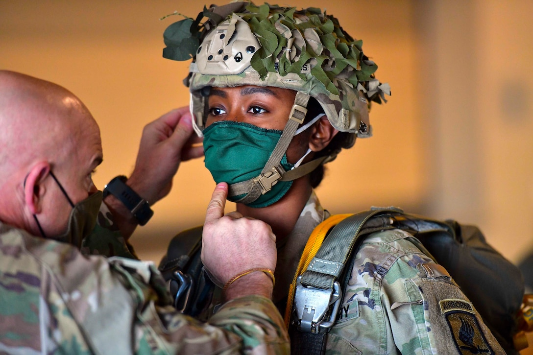 A soldier adjusts the helmet straps on another soldier; both wearing face masks.
