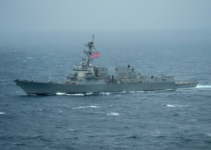 A guided-missile destroyer with an American flag raised moves through the Pacific Ocean.