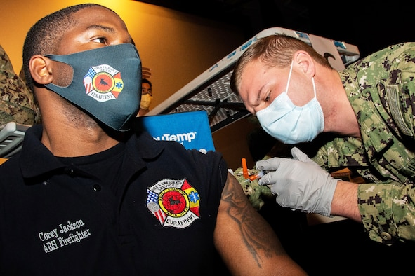 A Navy petty officer wearing a face mask and gloves gives a COVID-19 vaccine to a Navy seaman.