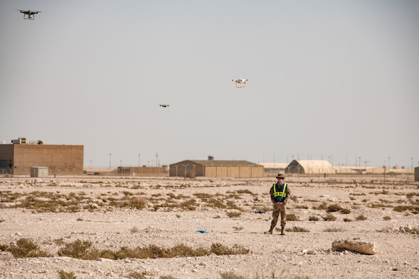 An Airman stands in a field surrounded by drones