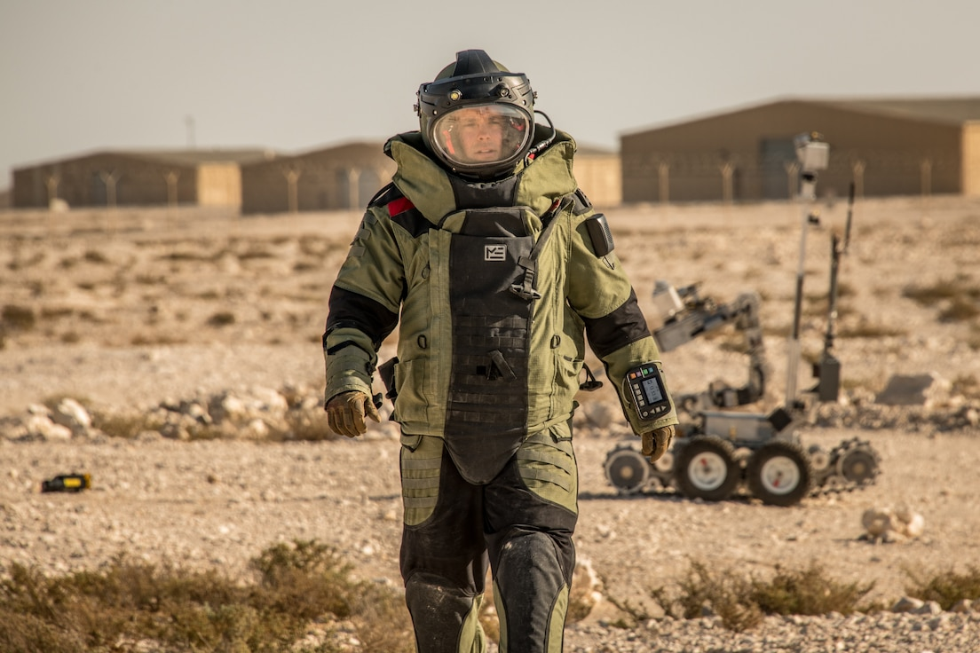 A man walks in an explosive ordnance disposal protection suit