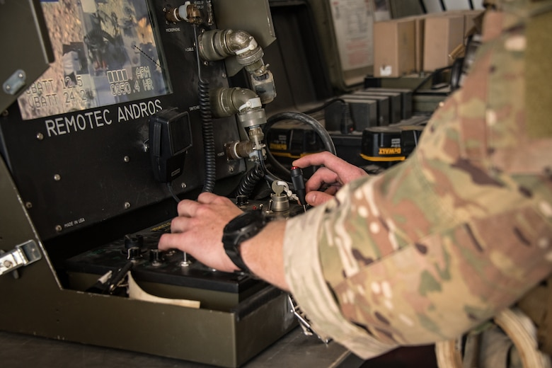 An Airman uses the controls of a remote driving system