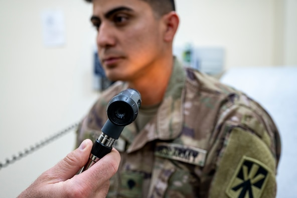 U.S. Army Private 1st Class Alvaro Corona, 380th Expeditionary Medical Group healthcare specialist, receives an exam for a shaving waiver at Al Dhafra Air Base, United Arab Emirates, Dec. 22, 2020.