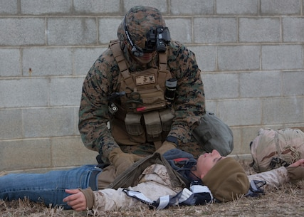 U.S. Navy Petty Officer 3rd Class Robert Mears, a corpsman with Charlie FAST Company, 5th Platoon, Marine Corps Security Force Regiment applies first aid to a notional gunshot wound during a Mission Readiness Exercise (MRX) Jan 13, 2021, on Fort A. P. Hill in Port Royal, Virginia. Fleet Antiterrorism Security Team (FAST) platoons execute MRX exercises prior to deployment to evaluate the platoons' proficiency in core mission essential tasks. (U.S. Marine Corps Photo by Sgt. Desmond Martin/Released)
