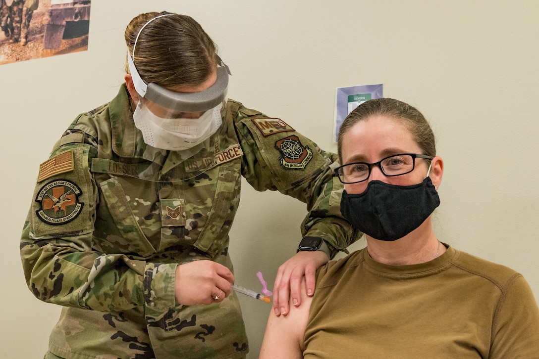 Lt. Col. Brittany Nutt, 436th Health Care Operations Squadron commander, is administered the COVID-19 vaccine by Staff Sgt. Kelsey Loeser, 436th Medical Group unit training manager, Jan. 15, 2021, at Dover Air Force Base, Delaware. Nutt was among the first Team Dover frontline workers who voluntarily received the vaccine in concurrence with Department of Defense guidance. The vaccine was granted emergency use authorization by the U.S. Food and Drug Administration for use in prevention of COVID-19. (U.S. Air Force photo by Roland Balik)