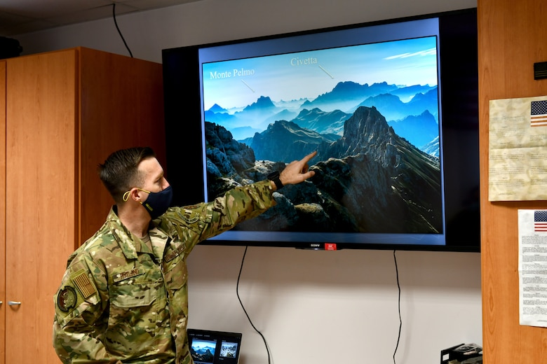 """U.S. Air Force Tech. Sgt. Michael Rutland, 31st Operations Support Squadron Survival, Evasion, Resistance and Escape (SERE) noncommissioned officer in charge, explains the purpose of the """"via ferrata"""" during SERE training at Aviano Air Base, Italy, Jan. 19, 2021. Italian for """"iron path"""", via ferrata is a system of metal cables or ladders that assist in climbing dangerous routes within the mountains. (U.S. Air Force photo by Staff Sgt. K. Tucker Owen)"""