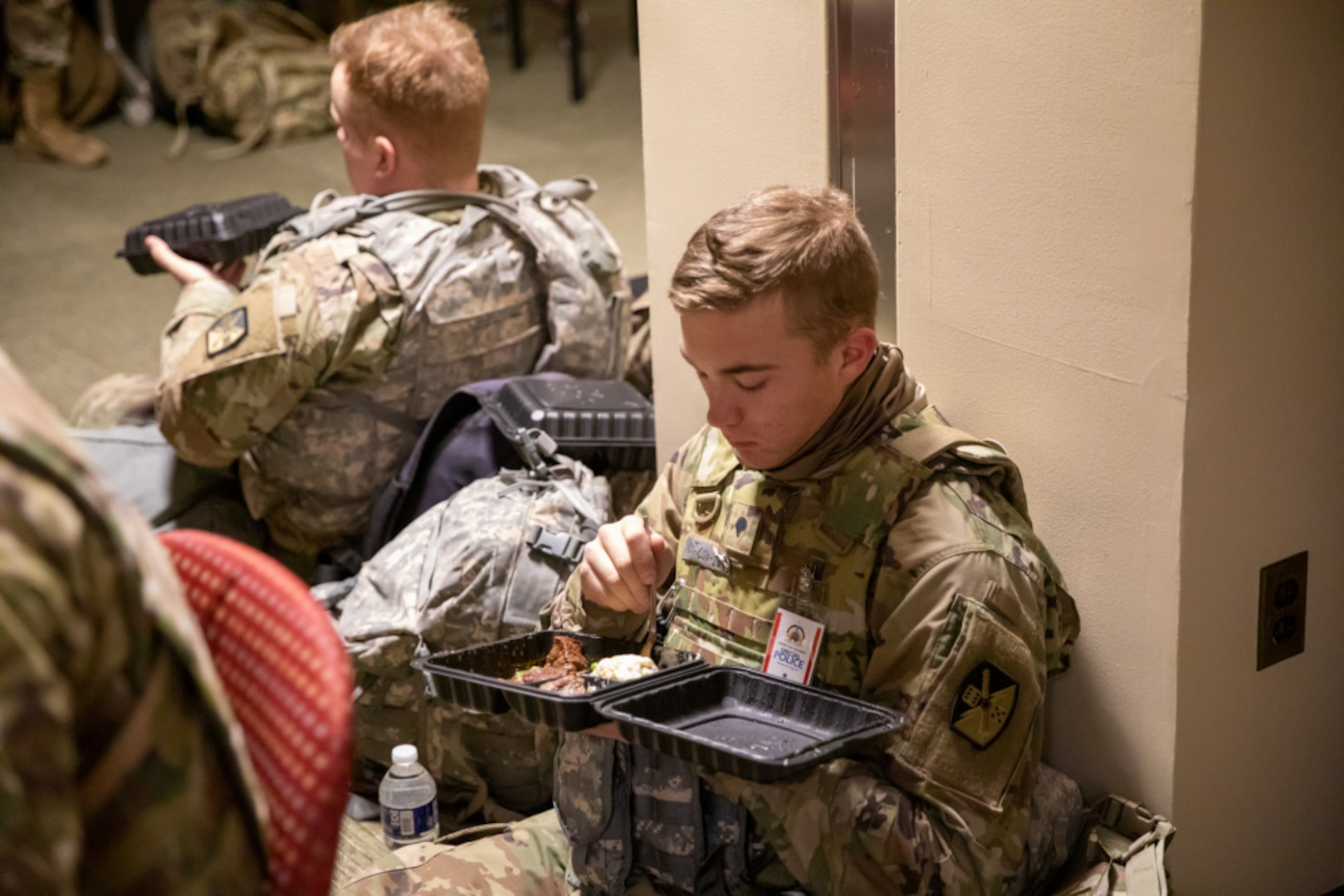A soldier sits in uniform leaning on a wall eating a meal.