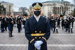 A soldier of the Army's Old Guard stands in the foreground of other soldiers all in service dress.