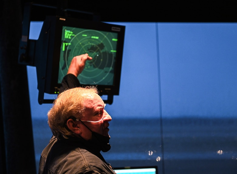 Retired U.S. Air Force Master Sgt. Walter Boltwood, Radar Approach Control (RAPCON) chief controller, points to a radar and chats with his peers on Jan. 7, 2020, at Columbus Air Force Base, Miss. Responsible for managing the flow of aircraft through all aspects of their flight, Air Traffic Control specialists ensure the safety and efficiency of air traffic on the ground and in the air. (U.S. Air Force photo by Airman 1st Class Davis Donaldson)