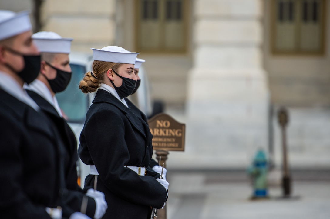 Service members wearing facemasks stand in formation.
