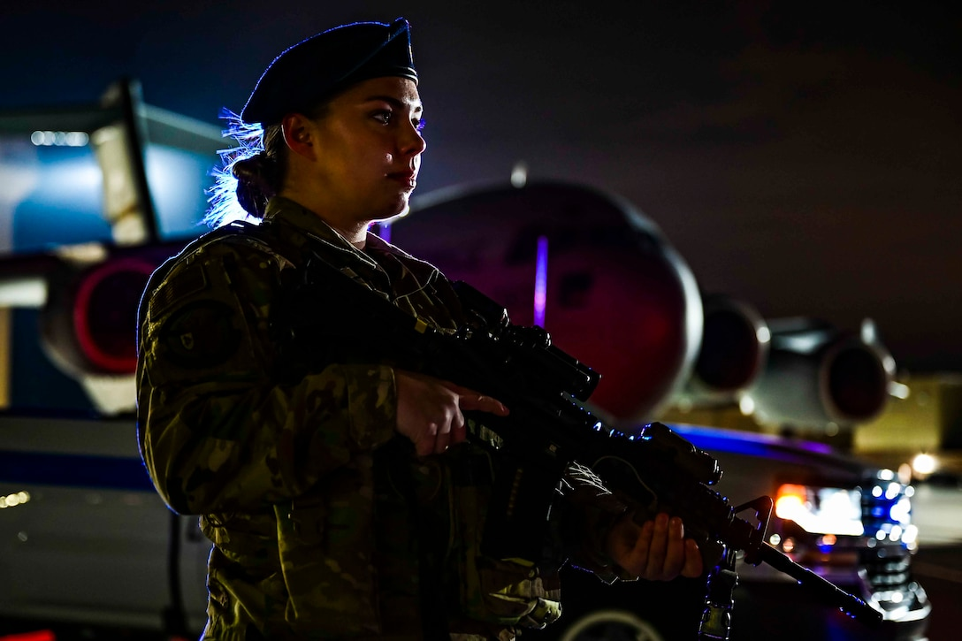 An airman holds a weapon while standing in front of an aircraft at night.