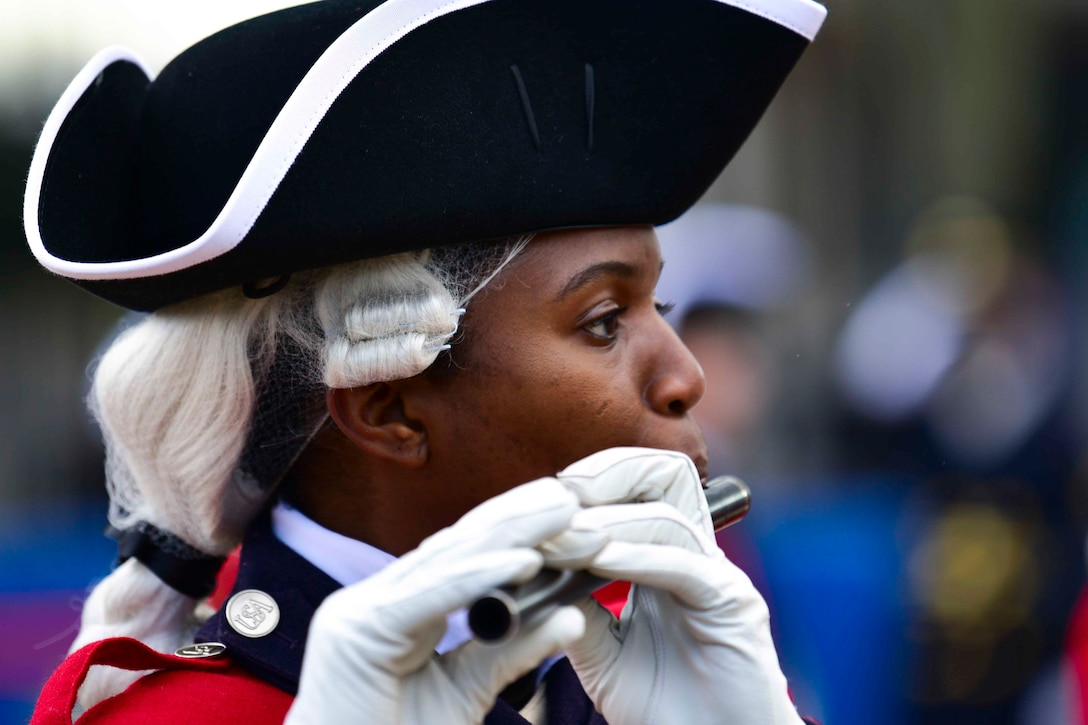 A soldier blows into an instrument.