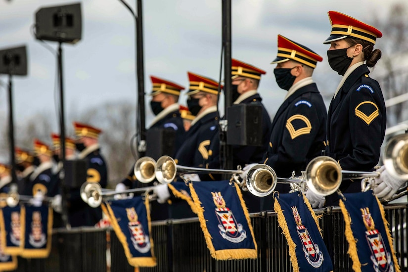 Band members stand in a line while carrying trumpets.