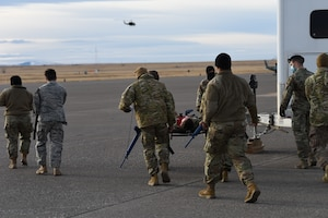 Convoy members escort an injured Airman towards a helicopter for evacuation.