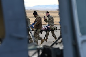 Convoy team members are escorting an injured Airmen on a stretcher towards a helicopter for evacuation.