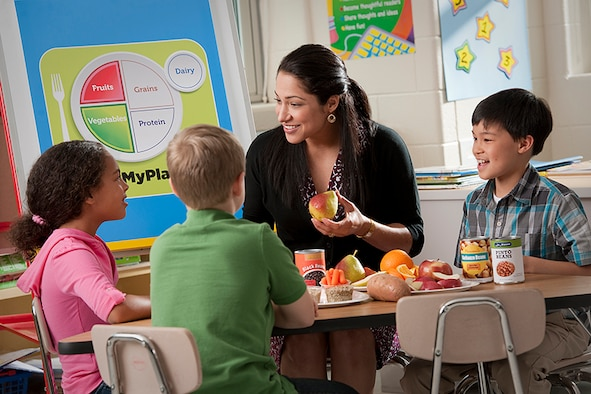 Woman eating with children with apple in her hands