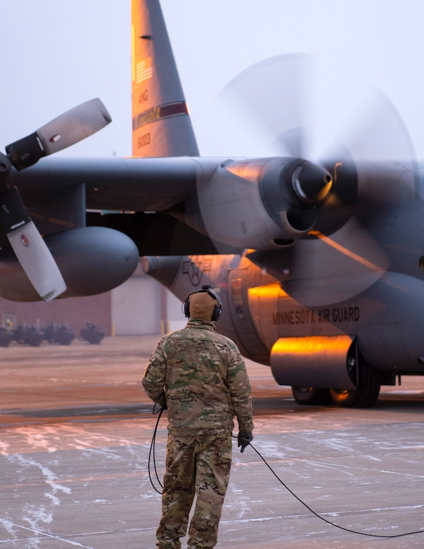 A loadmaster with the 109th Airlift Squadron watches C-130 Hercules start their engines in St. Paul, Minn., Jan. 18, 2021.