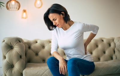 A woman sitting on a couch holding her lower back in pain.