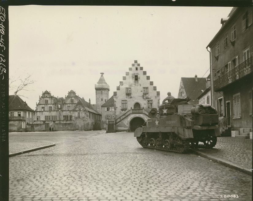 A historic photo shows a tank parked on the road and sidewalk of a deserted town.