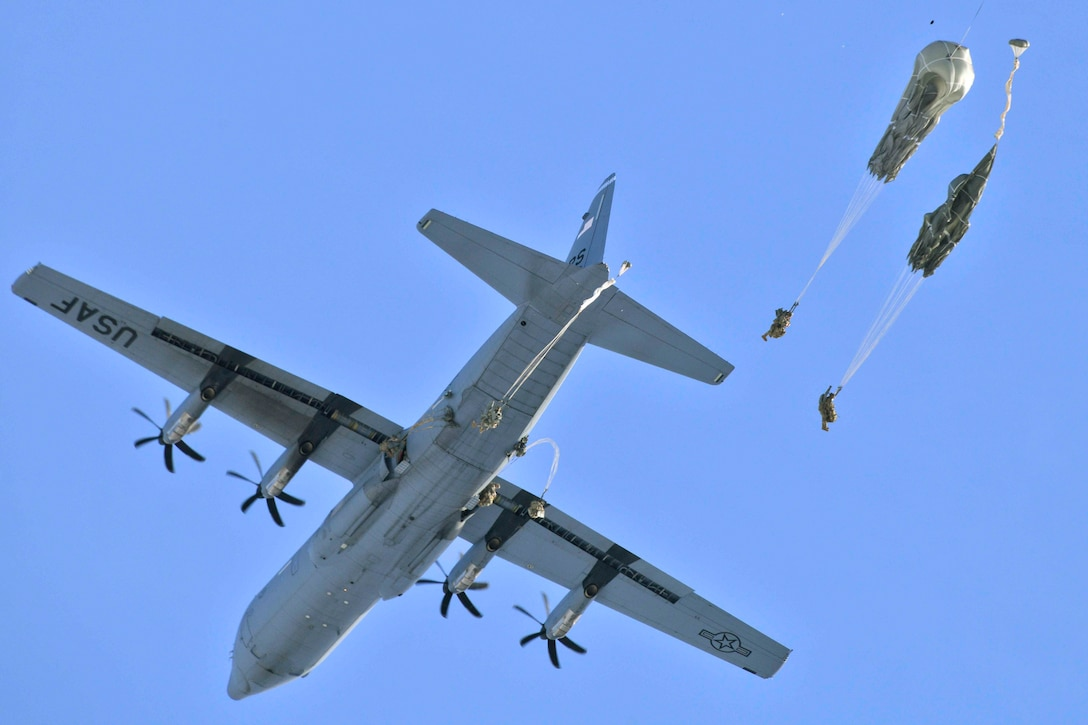 Two soldiers descend in the sky wearing parachutes after jumping from an aircraft.
